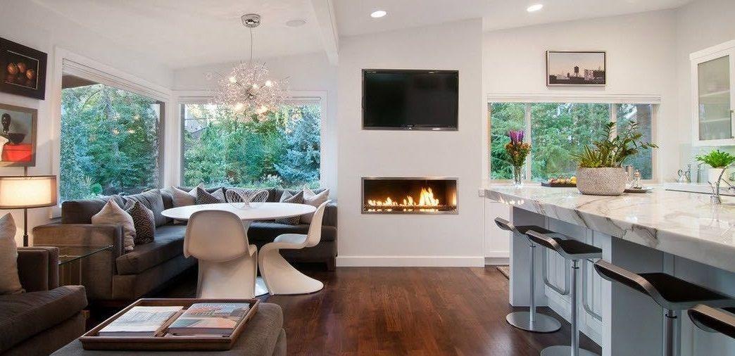 Интерьер гостиной с камином, совмещенной с кухней